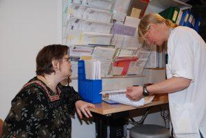 Fysioterapeut som blar i papirer og pasient som følger interessert med