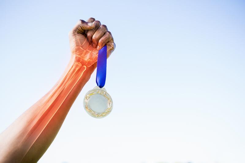 Arm hvor skjelettet lyser i rødt gjennom huden og tviholder på en medalje