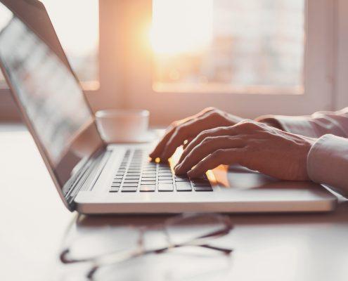 Hender som skriver på et laptoptastatur