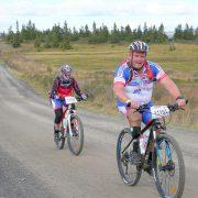 Mann og dama på sykkel på landeveien i sykkelklær