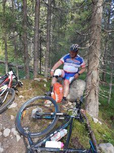Mann sitter på stein i skogen og justerer benprotese