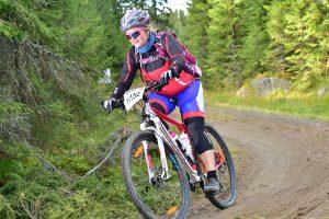Dame med startnummer sykler nedover i en sving