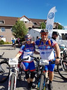 To mennesker med sykler smiler og holder rund hverandre i målområdet