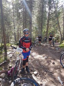 Dame står ved siden av sykkel mens mange sykkelryttere kommer gående opp en bakke bak