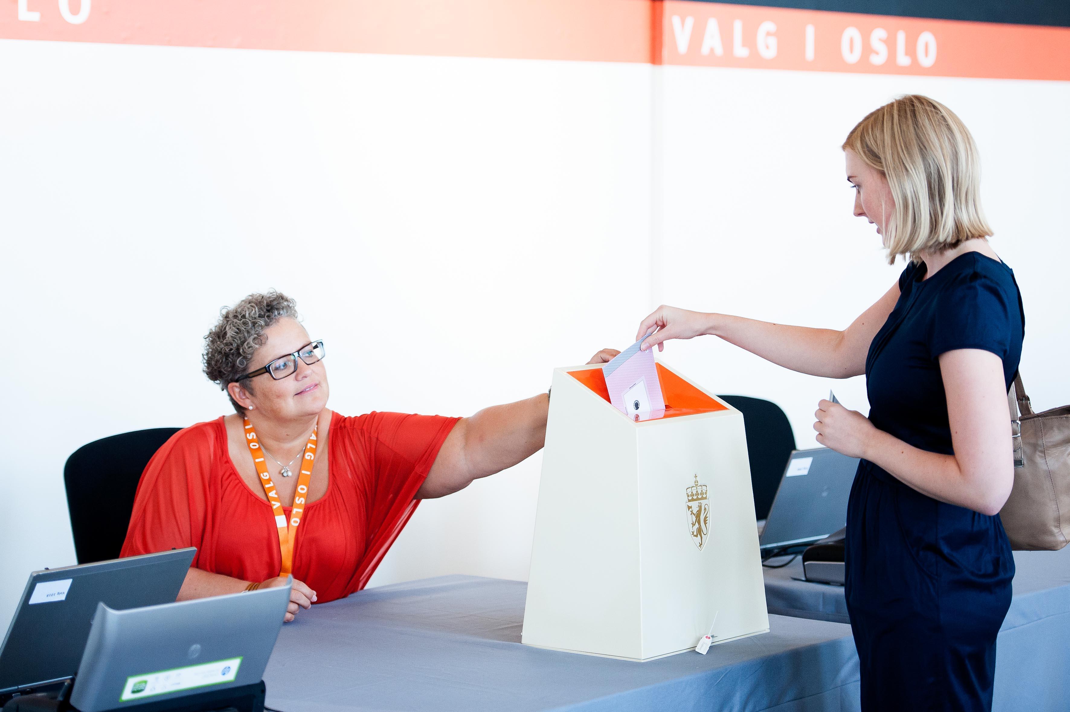 Ung kvinne legger forhåndsstemmeseddel i stemmeurne mens kvinnlig valgfunksjonær passer på