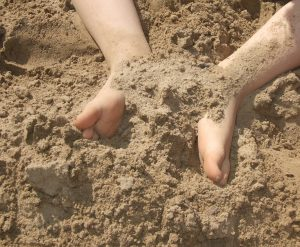 Føtter som har gravd i sand