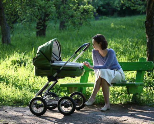 ung kvinne sitter på en benk og holder på en barnevogn