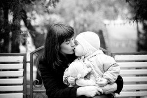 Mor på en benk som kysser sitt barn