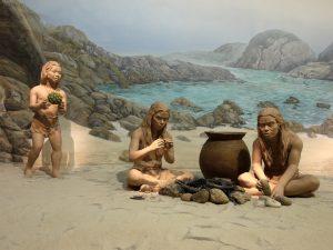 Steinalderfamilie ved utbrent bål ved sjøen