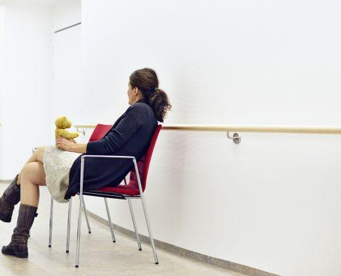 Kvinne venter i sykehuskorridor med bamse på kneet