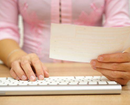 Kvinne betaler faktura ved et tastatur
