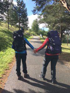 To turgåere sett bakfra med fulle sekker holder hverandre i hånden og går på en vei
