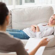 Kvinne ligger på sofaen hos en psykolog