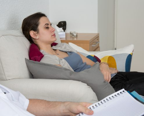 Kvinne ligger hos psykologen med lukkede øyne