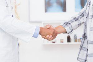 Lege og pasient gir hverandre håndtrykk