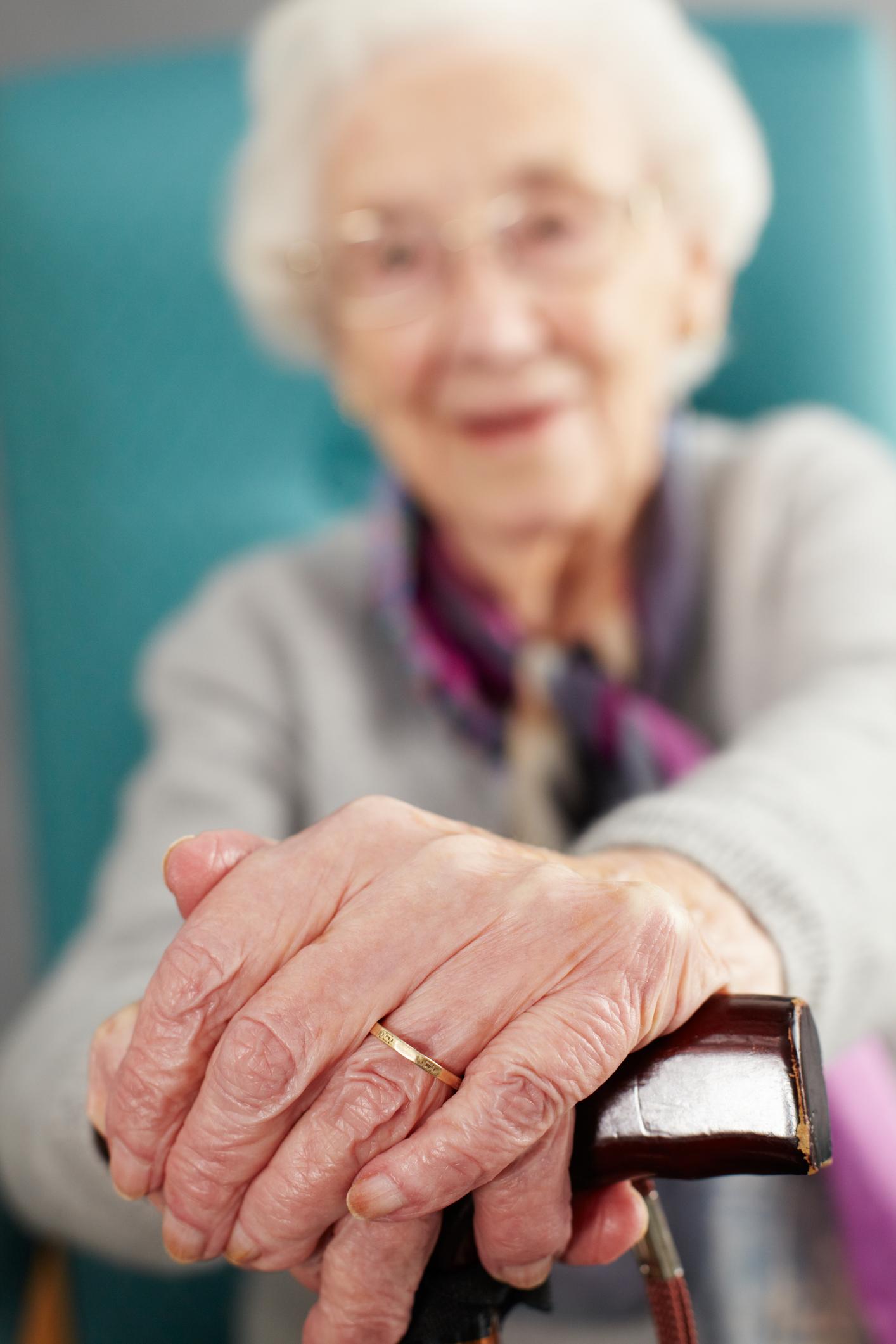 Eldre dame som lener seg på en stokk