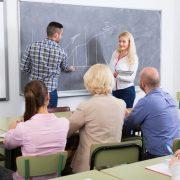 Voksne i et klasserom med lærer