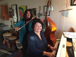 Kvinne ved pianoet og en kvinne bak med fiolin