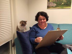 Kvinne sitter i sofaen og tegner mens katten sitter og ser på
