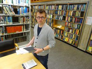 Mann som står i bibliotekt med bøker og papirer i hendene