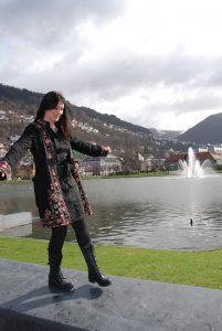Kvinne som balanserer på en mur med vann i bakgrunnen