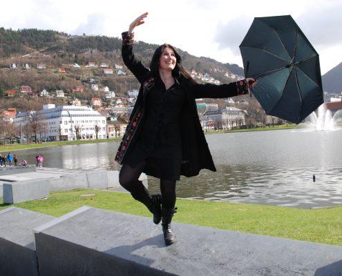 Kvinne i ballettposisjon med oppslått paraply