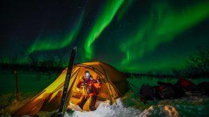 Kvinne i gult telt i snøen med masse grønt nordlyspå himmelen