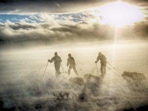 Tre mennesker på ski i tåke
