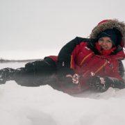 Kvinne ligger på isen og fisker i vinterklær