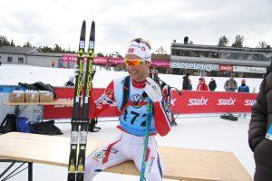Sjur Røthe sitter på en benk med ski ved siden av seg