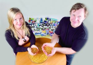 To personer løfter ut never med fiskeoljekapsler fra en diger bolle
