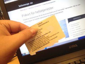 Gult frikort tak 2 foran en dataskjerm med helsenorge.no