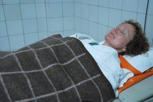 Kvinne innpakket i tepper på en benk