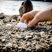 En hånd som plukker en hvit stein på steinstrand