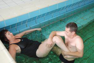 Kvinne får individuell fysio i basseng av en mannlig fysioterapeut