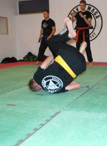 Mann ruller på matte i treningssal