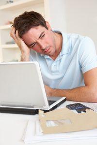 Mann tenker ved laptop