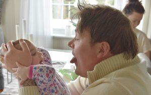 Mann rekker tunge til babyen han holder foran seg