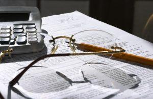 Kalkulator, briller og blyant ligger på papirer