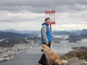 Kvinne og hund på toppen av et fjell med flott utsikt
