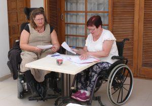 To kvinner i rullestol fyller ut papirer søknadspapirer