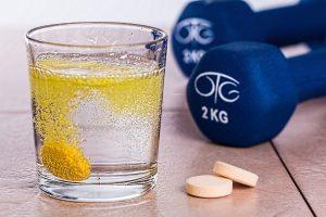 Glass med vitaminer som løses opp i vann og små vekter