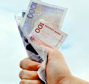 Norske pengesedler klemmes i en hånd