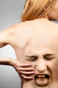 Illustrasjon av skrikende ansikt på en kvinnes rygg