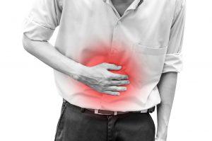 Mann holder seg på magen, som har rød markering for smerte