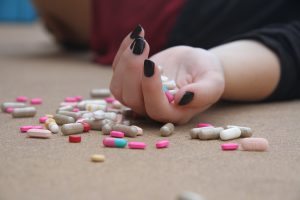 Hånd med mange ulike piller i og på bordet