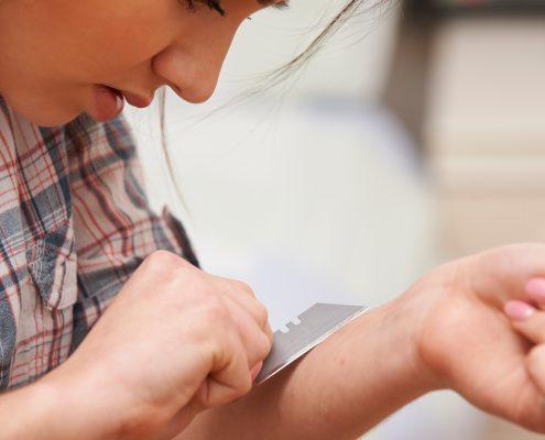 Ung kvinne med knivblad mot underarmen