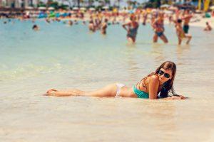 Ung kvinne soler seg i vannet/strandkanten