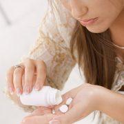 Ung kvinne heller piller i en hånd