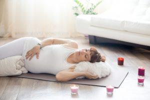 Gravid kvinne ligger på gulvet